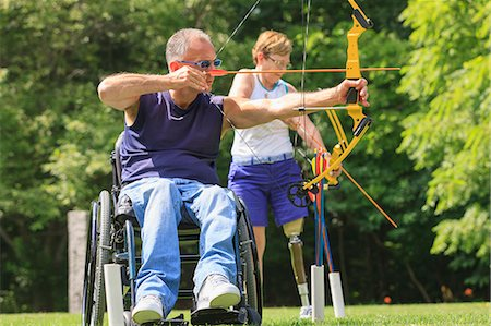 Man with spinal cord injury and woman with prosthetic leg during archery practice Stock Photo - Premium Royalty-Free, Code: 6105-08211288