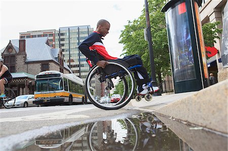 Man in wheelchair with Spinal Meningitis going over a curb Stock Photo - Premium Royalty-Free, Code: 6105-08211234