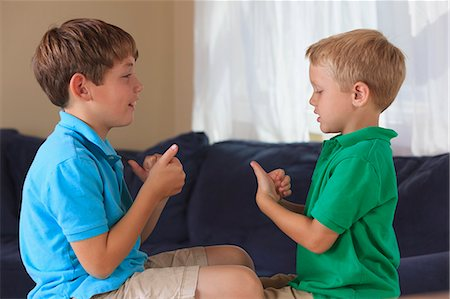 Boys with hearing impairments signing 'sports' in American sign language on their couch Stock Photo - Premium Royalty-Free, Code: 6105-08211323