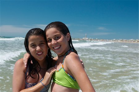 Two girlfriends, embracing on beach, smiling, port Stock Photo - Premium Royalty-Free, Code: 6106-05394641