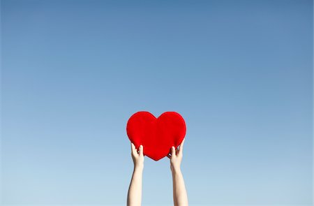 Hand of a woman lifting red heart,against blue sky Stock Photo - Premium Royalty-Free, Code: 6106-05395055