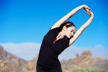 stretching (people exercising) - Caucasian female stretching in volcanic area Stock Photo - Premium Royalty-Free, Code: 6106-05442289