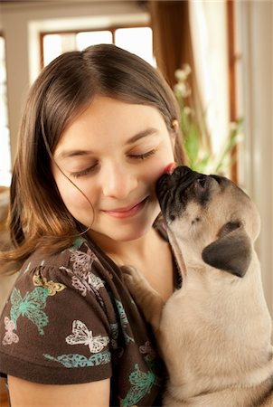 dog lick - Little Girl Being Kissed by a Pug Puppy. Stock Photo - Premium Royalty-Free, Code: 6106-05442379