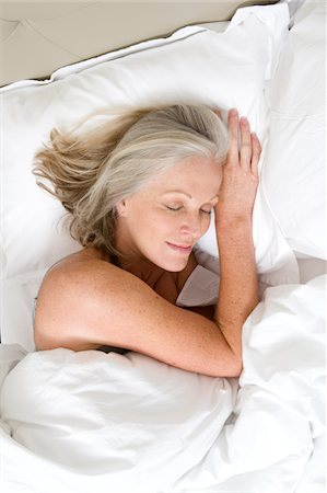 Mature woman sleeping in bed Stock Photo - Premium Royalty-Free, Code: 6106-05442529