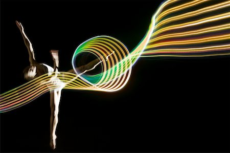 dancer on tip toes in golden glowing light trail Stock Photo - Premium Royalty-Free, Code: 6106-05443426