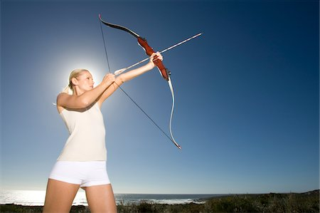 Female archer standing at sea shore aiming arrow Stock Photo - Premium Royalty-Free, Code: 6106-05443710