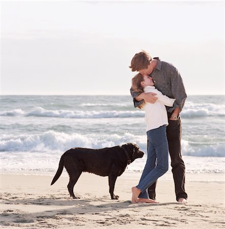 preteen kissing - Girl (10-12) embracing father on beach next to black labrador Stock Photo - Premium Royalty-Free, Code: 6106-05452507