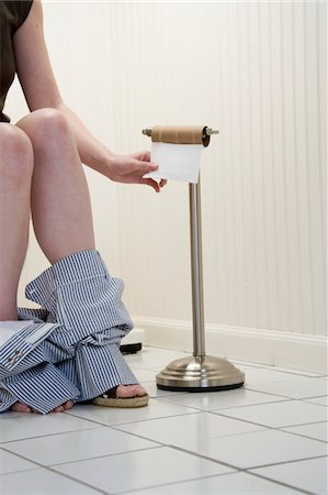 Young woman sitting on toilet, by empty loo roll, low section Stock Photo - Premium Royalty-Free, Code: 6106-05452637