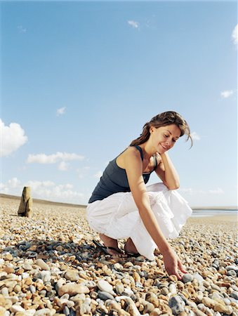 Young woman crouching on pebble beach, picking up pebbles, smiling Stock Photo - Premium Royalty-Free, Code: 6106-05453017