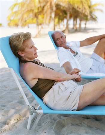 seniors woman in swimsuit - Senior couple relaxing on sun loungers on beach, holding hands Stock Photo - Premium Royalty-Free, Code: 6106-05453276