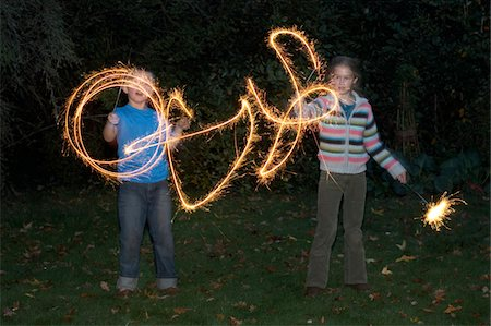 Girl and boy (7-9) playing with sparklers in garden, night Stock Photo - Premium Royalty-Free, Code: 6106-05453657