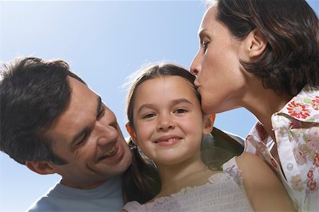 daughter kissing mother - Couple embracing daughter (5-7) smiling, portrait, close-up Stock Photo - Premium Royalty-Free, Code: 6106-05454133