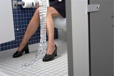 Businesswoman sitting on toilet writing on tissue paper Stock Photo - Premium Royalty-Free, Code: 6106-05455321