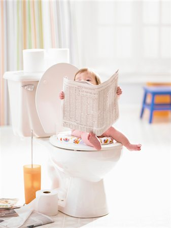 Male toddler (12-15 months) on toilet holding newspaper Stock Photo - Premium Royalty-Free, Code: 6106-05456301