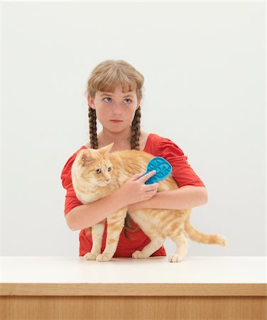 preteen girl pussy - Girl (9-11) with arms around cat standing on table Stock Photo - Premium Royalty-Free, Code: 6106-05456584