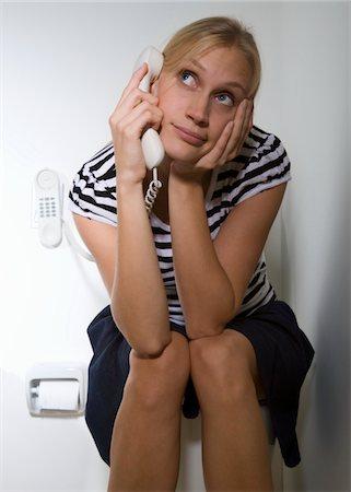 Woman sitting on toilet, using telephone Stock Photo - Premium Royalty-Free, Code: 6106-05457171