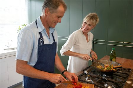 Mature couple cooking in kitchen, smiling Stock Photo - Premium Royalty-Free, Code: 6106-05459422