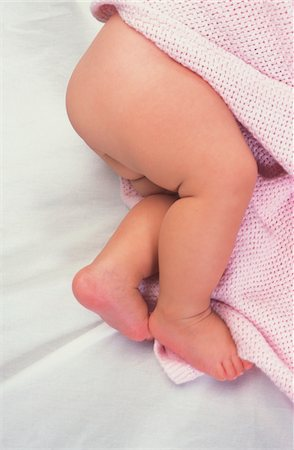 Baby girl (3-6 months) lying on bed, close-up Stock Photo - Premium Royalty-Free, Code: 6106-05466046