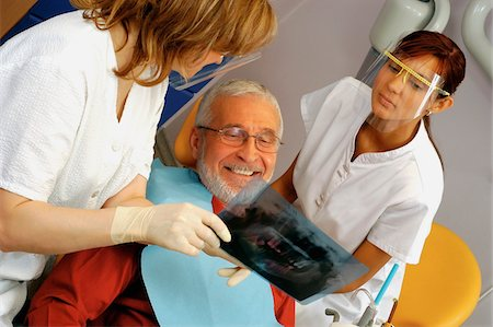 Two female dentists showing an X-Ray to a male patient Stock Photo - Premium Royalty-Free, Code: 6106-05466089
