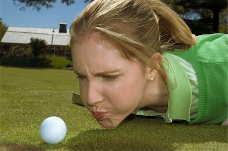Frustrated woman blowing on golf ball, close-up Stock Photo - Premium Royalty-Free, Code: 6106-05466568