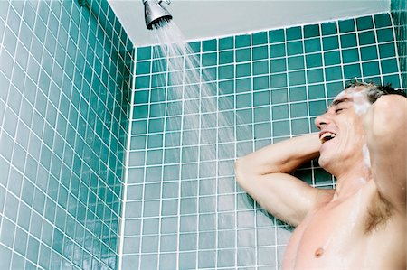 Low angle view of a young man bathing Stock Photo - Premium Royalty-Free, Code: 6106-05466674