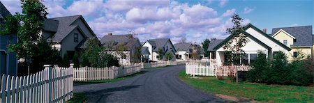 This is a typical suburban American neighborhood. There are single family homes with a white picket fences in front of each house. A road leads down the center of the image that takes you past each house. There are trees beside each house. Stock Photo - Premium Royalty-Free, Code: 6106-05472451