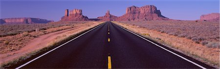 This is Route 163 that runs through the Navajo Indian Reservation. The road runs large through the middle and gets smaller as it heads toward the rocks. The red rocks of Monument Valley are in the background. The scrub plants of the desert are on either s Stock Photo - Premium Royalty-Free, Code: 6106-05472598
