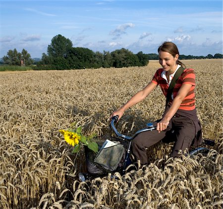 riding crop - Woman riding bicycle on wheat field Stock Photo - Premium Royalty-Free, Code: 6106-05473554