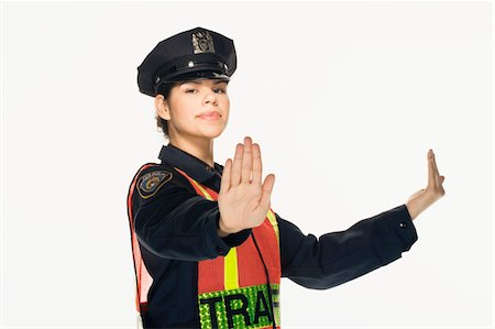 female police officer happy - Traffic police officer directing traffic on white background, portrait Stock Photo - Premium Royalty-Free, Code: 6106-05476589