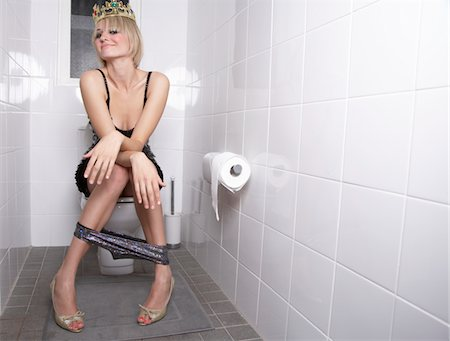 Young woman wearing crown sitting on toilet, smiling, portrait Stock Photo - Premium Royalty-Free, Code: 6106-05481679
