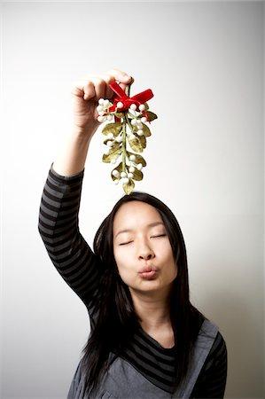 Young woman holding mistletoe, pursing lips, eyes closed Stock Photo - Premium Royalty-Free, Code: 6106-05484501