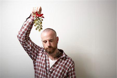 Young man holding mistletoe, eyes closed Stock Photo - Premium Royalty-Free, Code: 6106-05484513