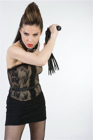 Female dominatrix with whip, portrait Stock Photo - Premium Royalty-Free, Code: 6106-05484670