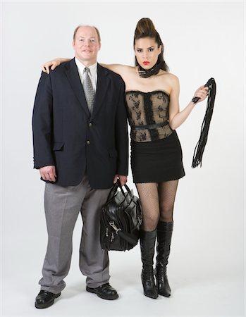 Dominatrix embracing businessman, portrait Stock Photo - Premium Royalty-Free, Code: 6106-05484711