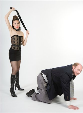 Dominatrix preparing to whip businessman, studio shot Stock Photo - Premium Royalty-Free, Code: 6106-05484712