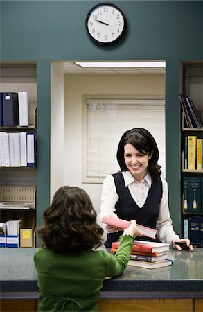 education loan - Girl (8-9) giving books to librarian in library Stock Photo - Premium Royalty-Free, Code: 6106-05485540