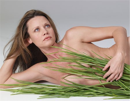 Mature naked woman lying on floor holding grass Stock Photo - Premium Royalty-Free, Code: 6106-05486023