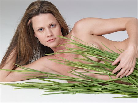 Mature woman lying naked on floor holding grass, portrait Stock Photo - Premium Royalty-Free, Code: 6106-05486022