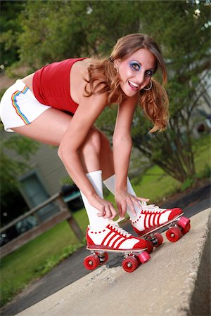 roller skate - Woman bending over to tie her skate Stock Photo - Premium Royalty-Free, Code: 6106-05486515