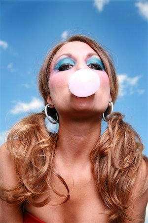 Woman blowing a bubble Stock Photo - Premium Royalty-Free, Code: 6106-05486518