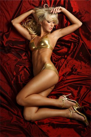 Young sensual woman in gold lingerie on red bed Stock Photo - Premium Royalty-Free, Code: 6106-05486609