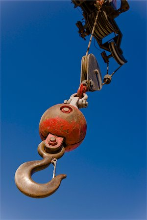 Look up at a hook, ball and pulley on a crane in morning sun. Stock Photo - Premium Royalty-Free, Code: 6106-05487127