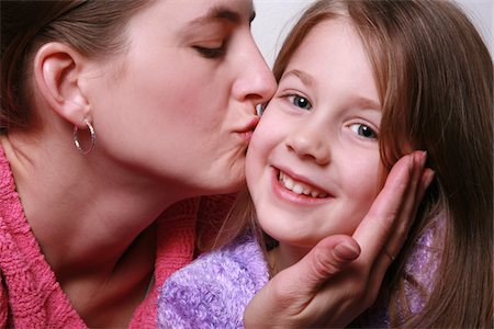 daughter kissing mother - A mother kissing her smiling 5 year old daughter on the cheek Stock Photo - Premium Royalty-Free, Code: 6106-05487710