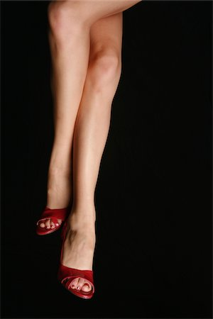 A pair of woman's legs isolated on black. Stock Photo - Premium Royalty-Free, Code: 6106-05487964