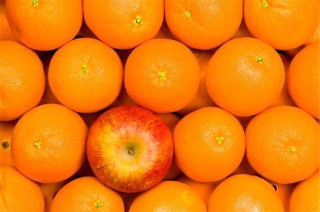 One red apple among rows of fresh oranges Stock Photo - Premium Royalty-Free, Code: 6106-05488973