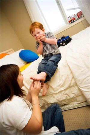 a mother tickles her son's feet. Stock Photo - Premium Royalty-Free, Code: 6106-05489213
