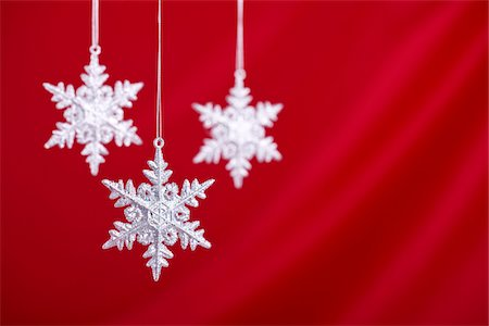 snowflakes  holiday - Silver snowflakes against a red silk backdrop.  Shallow depth of field/selective focus on front snowflake. Stock Photo - Premium Royalty-Free, Code: 6106-05490863