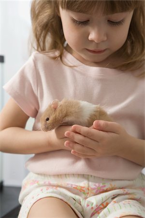 Little girl playing with her hamster Stock Photo - Premium Royalty-Free, Code: 6106-05492183