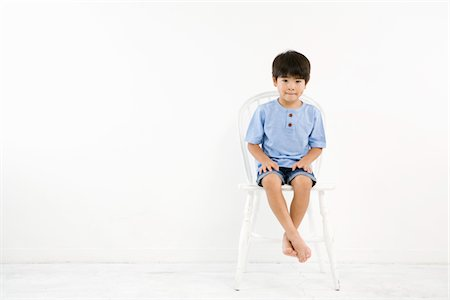 A boy is sitting on white chair in front of wall Stock Photo - Premium Royalty-Free, Code: 6106-05493026