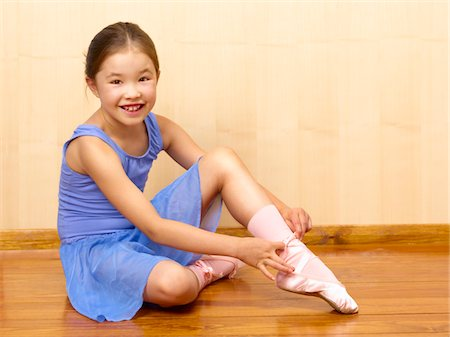 Child Ballerina tying ballet shoes Stock Photo - Premium Royalty-Free, Code: 6106-05493527
